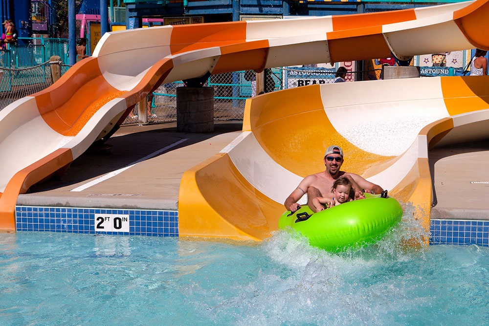 Father and little girl on sliding on water tube at big top, water world