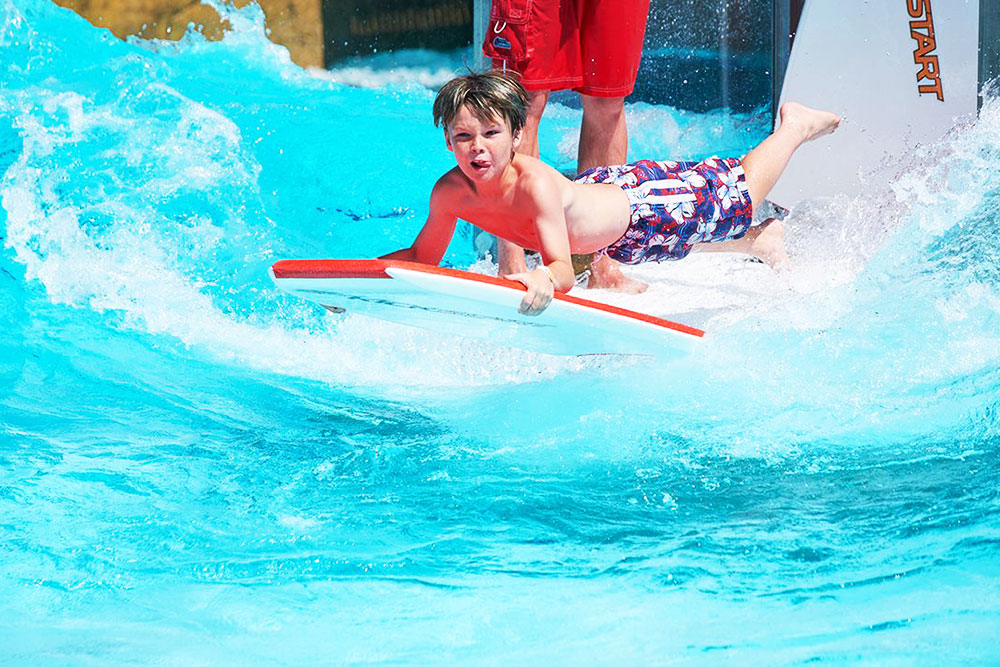 Boy on water board riding wave at cowabunga beach, Water World