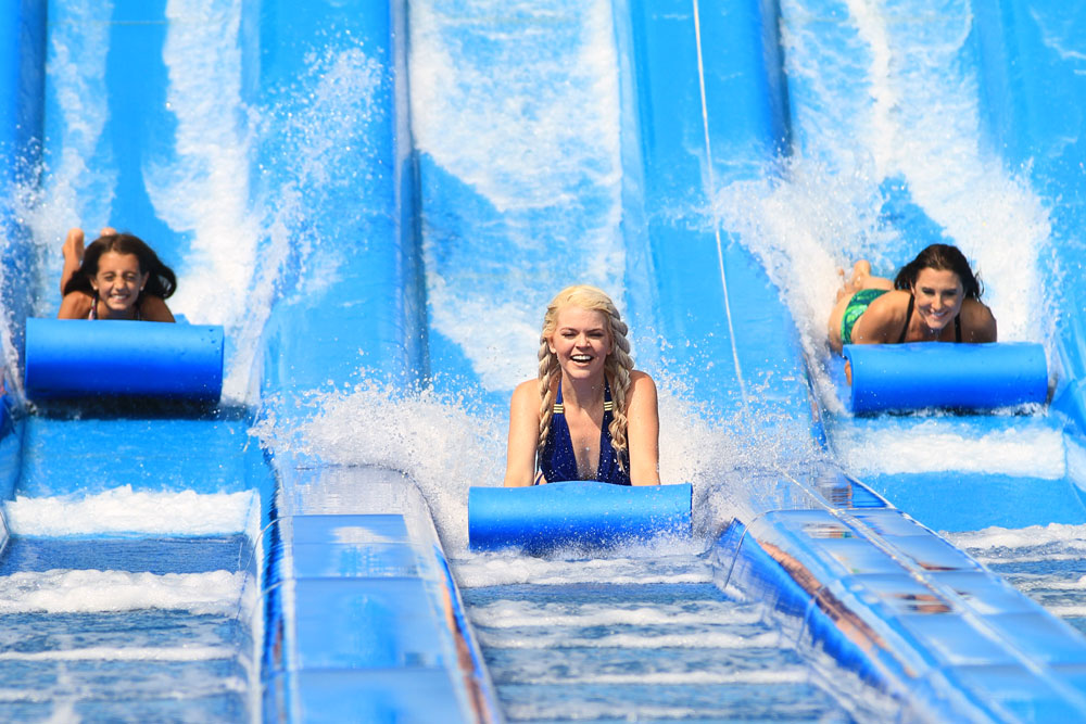 Three girls sliding at Glacier Run, Water World