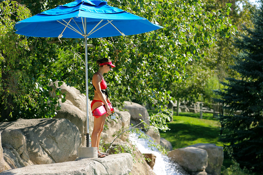 Woman lifeguard on watch under sun umbrella