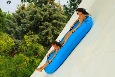 Zoomerang attraction, mother and daughter sliding on water tube, water world